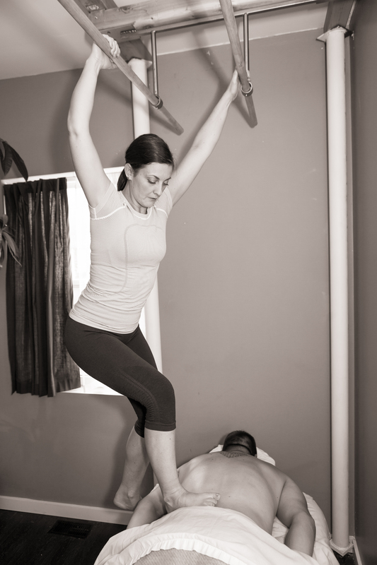 Ashiatsu massage therapist using her feet to massage the client's back, spine, and muscles.